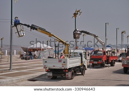 NONG KHAI, THAILAND - October 24, 2015: Worker Work in the basket on electricity post at Mueang Nong Khai Municipality, Thailand