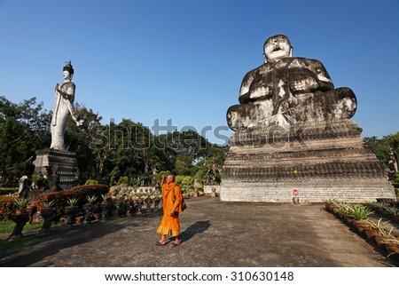 NONGKHAI, THAILAND- NOV 2 : Unidentified buddhist monk walk around the old Buddha statues park at Sala Kaeo Ku on November 2, 2010 in Nongkhai. It is a Buddha idol and shrines all 208 elements - stock photo