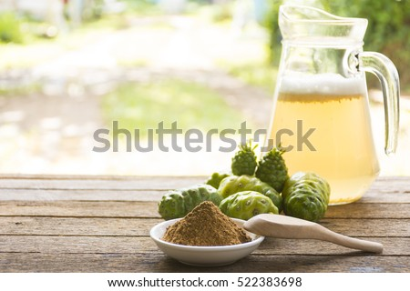 Noni fruit  and noni juice with noni powder on wooden table.Fruit for health and herb for health.