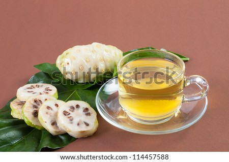 Noni juice fresh on brown background - stock photo