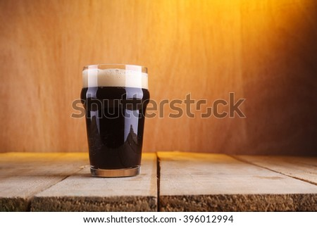 Nonic pint glass with dark stout beer on a grunge wood background