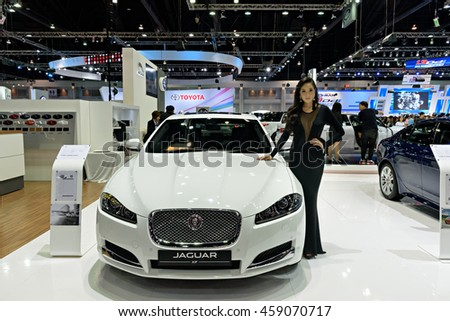 NONTHABURI, THAILAND - DECEMBER 13: Unidentified female models post at the the Jaguar XF booth during the 32nd Thailand International Motor Expo 2015 on December 13, 2015 in Nonthaburi, Thailand.