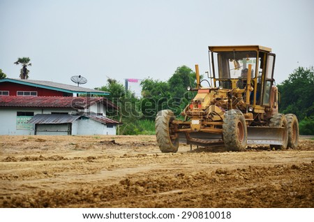 NONTHABURI, THAILAND - JUNE 12 : Motor grade machine and people working at construction site on June 12, 2015 in Nonthaburi, Thailand. - stock photo