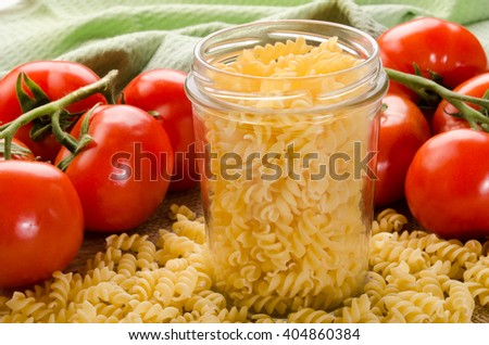 noodle in a storage glass and fresh tomato - stock photo