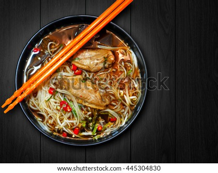 Noodle with chicken in black bowl and orange chopsticks on black wood background with clipping path. Spicy noodle. Still life. Copy space.