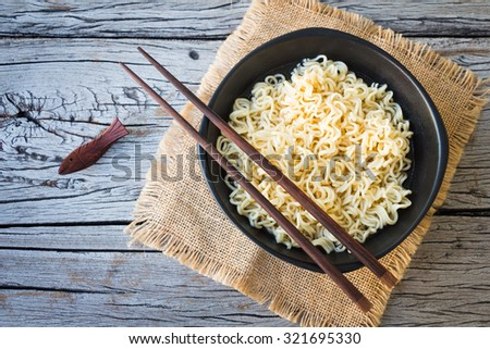 Noodles in a black bowl on a wooden table background. - stock photo