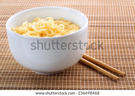 noodles in a bowl over a bamboo place-mat - stock photo