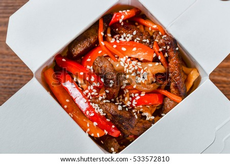 Noodles in a white box on a wooden background close up shot