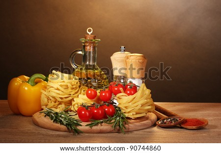 noodles in bowl, jar of oil, spices and vegetables on wooden table on brown background - stock photo