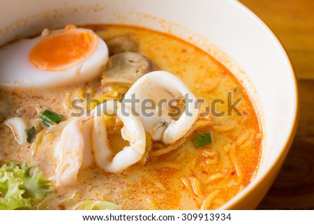 Noodles in thai spicy tom yum soup with squid