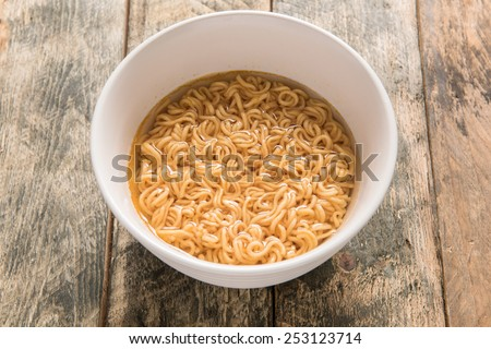 noodles in white dish on wooden background - stock photo