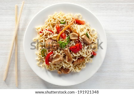 noodles with chicken and vegetables on white plate - stock photo