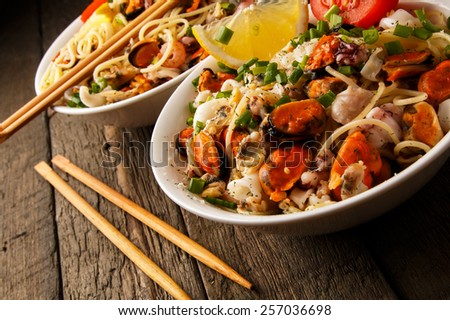 Noodles with seafood on wooden table