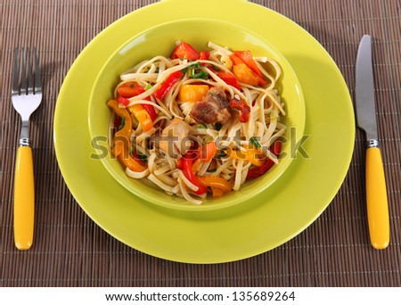 Noodles with vegetables on plate on wooden mat close-up