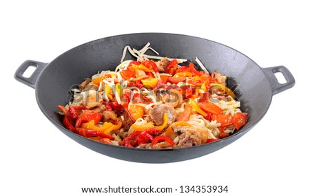 Noodles with vegetables on wok isolated on white