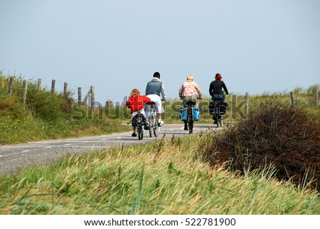 NOORDWIJK, NETHERLANDS - AUGUST 21, 2007: A family cycling in the fields, near the beaches
