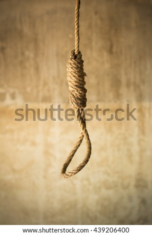 Noose in prison and wall grunge grain texture,Loop of old rope on wall background, Suicide concept Image in Studio with vignette lighting and copy space. - stock photo