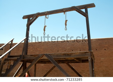 nooses hanging from a gallows - stock photo
