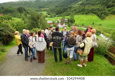 NORDDAL - JUNE 26: Russian tourists stand on hill and listen guide on JUNE 26, 2011 in Norddal, Norway. In 2011 Norway issued to Russian citizens 30 236 visas, 65% of visas were tourist.