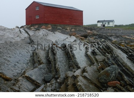 Nordic fisherman shacks by the shore with geological formations - stock photo