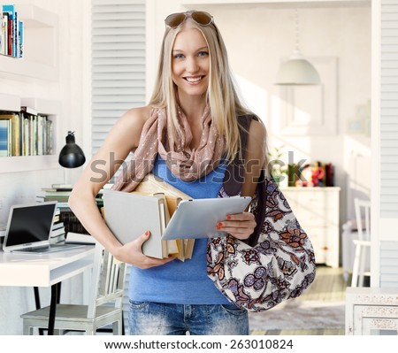 Nordic type college student leaving for school, holding books, and tablet, smiling happy.