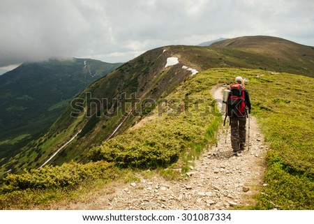 Nordic walk on the mountain road. Woman with trekking sticks under the clouds  - stock photo