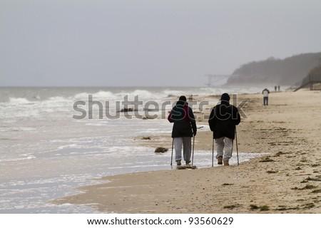 Nordic walking couple - autumn baltic sea, Poland - stock photo