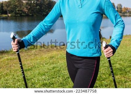 Nordic walking exercise adventure hiking concept - closeup of woman's torso and hands holding nordic walking poles - stock photo