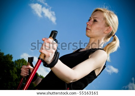 Nordic Walking - Young woman is hiking against blue sky.