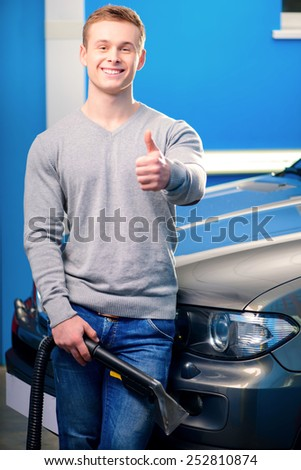 Normal Saturday of car owner. Closeup of handsome smiling young man standing by his luxury auto and showing his thumb up while holding a car vacuum cleaner in car service - stock photo