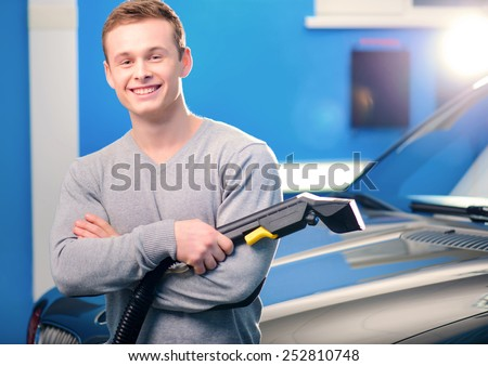 Normal Saturday of car owner. Closeup of handsome smiling young man standing by his luxury car with his hands crossed while holding a car vacuum cleaner car service - stock photo