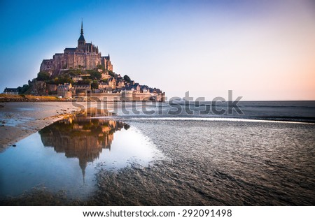 Normandy, France. Le Mont Saint Michel reflecting itself into the sea during sunrise. - stock photo