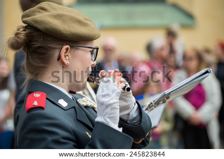 NORRKOPING, SWEDEN - JUNE 6: Female flutist in a military orchestra entertains during National day celebrations on June 6, 2014 in Norrkoping. The national day of Sweden is an official holiday. - stock photo