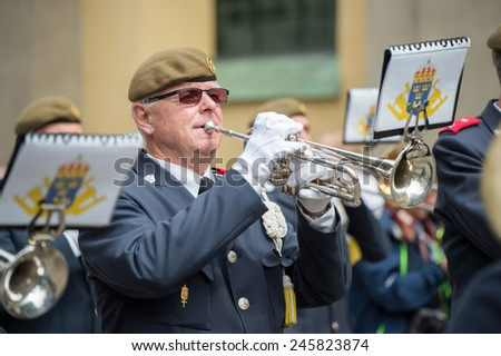 NORRKOPING, SWEDEN - JUNE 6: Male trumpet player in a military orchestra entertains during National day celebrations on June 6, 2014 in Norrkoping. The national day of Sweden is an official holiday. - stock photo