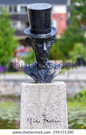 NORRTALJE, SWEDEN - JULY 11, 2015: Sculpture of Nils Ferlin in front view at the city center of Norrtalje. Several statues of Nils Ferlin have been erected in Sweden. - stock photo