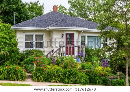 North American home from the sixites or seventies with an extensively landscaped yard. - stock photo
