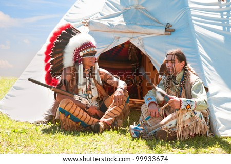 North American Indians sit at a wigwam - stock photo
