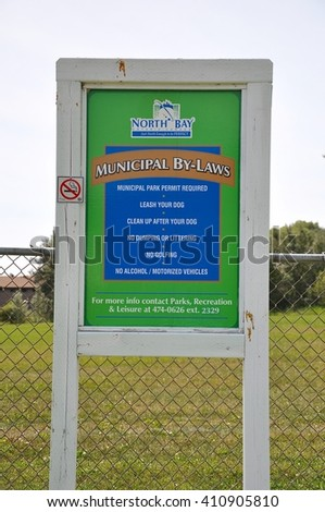 North Bay, Ontario, Canada - July 29, 2015: Municipal by-laws of North Bay posted in the park. - stock photo