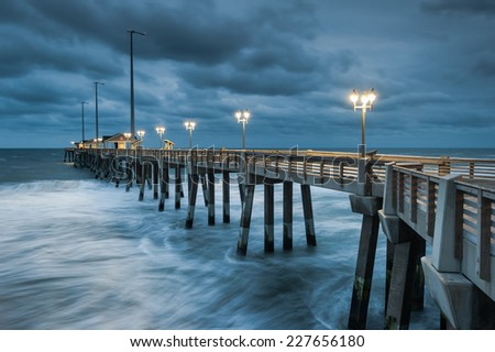 North Carolina Outer Banks OBX Fishing Pier Stormy Atlantic Ocean Morning in Nags Head - stock photo