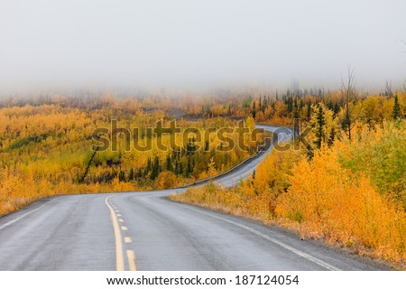North Klondike Highway winding through autumn gold colored boreal forest taiga countryside with low cloud cover, Yukon Territory, Canada - stock photo