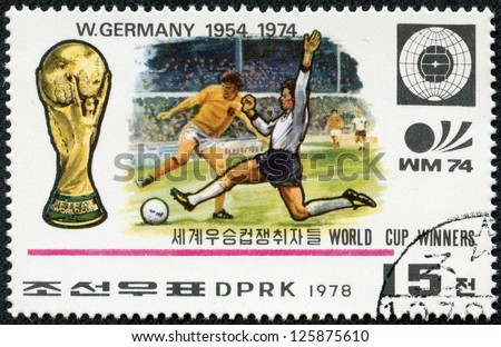 NORTH KOREA - CIRCA 1978: A Stamp printed in NORTH KOREA shows the Soccer players, Cup, Emblem and Globe, Germany (1954, 1974), World Cup Winners, circa 1978 - stock photo