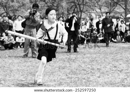 NORTH KOREA - MAY 1, 2012: Pioneer Korean girl with a bate plays the game due to the celebration of the Internationa Worker's Day in N.Korea, May 1, 2012. May 1 is a national holiday in 80 countries