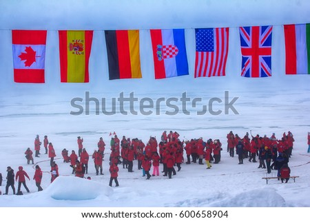 North pole - 2 July 2016: Mission is over: flags of all participating countries tremble at the North pole. Back guards against polar bears