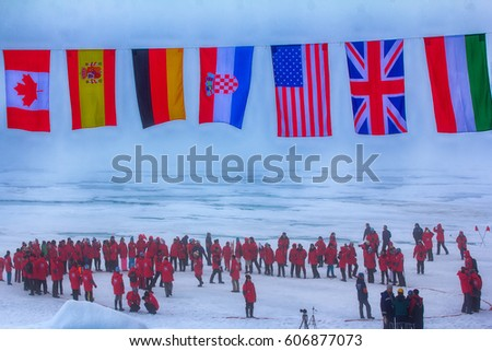 North pole - 2 July 2016: Mission is over: flags of all participating countries tremble at the North pole. Participants line up in circle of world around pole point - another 	circle of latitude