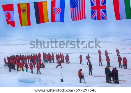 North pole - 2 July 2016: Mission is over: tourists made the world round (around the North pole point), flags of all participating countries tremble at the North pole. Back guards against polar bears