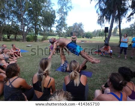 NORTH SHORE, HAWAII - FEBRUARY 26: AcroYoga Teacher Jason Nemer balances instructor as class watches demonstration at Wanderlust yoga event on the North Shore, Hawaii on February 26, 2016. - stock photo