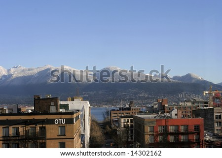 North Shore Mountains with first snow from downtown Vancouver - stock photo