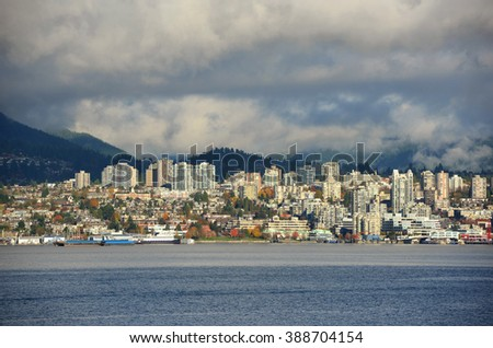 North Vancouver city skyline across Vancouver Harbour in a cloudy day, Vancouver, British Columbia, Canada. - stock photo