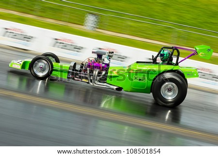 """NORTHAMPTONSHIRE, UK - JULY 15 2012: Dave Williams drive his dragster """"Chariot of Fire VI"""" at the Dragstalgia event at Santa Pod Raceway on 15th July.2012 - stock photo"""