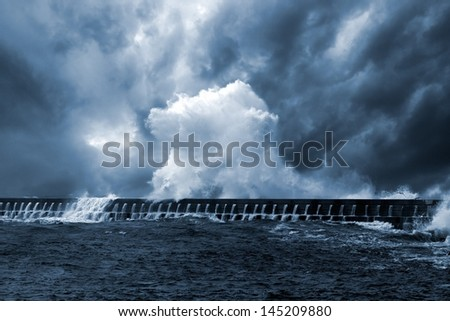 Northeast Atlantic storm waves over pier, Portugal - enhanced sky - stock photo